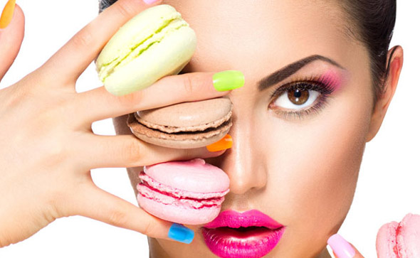 woman holding colorful cakes wearing colorful make up