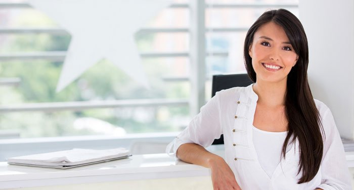 smiling woman in white at the counter