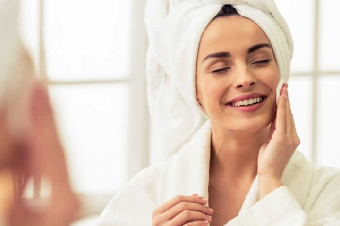 smiling woman wiping her soft face skin