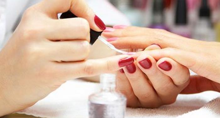 getting a pink nail polish application